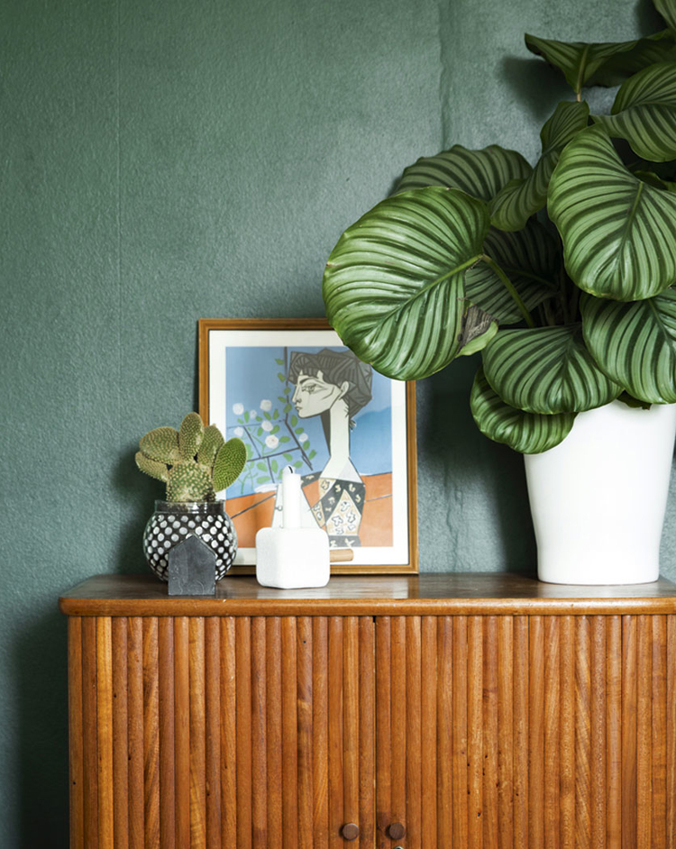dark green walls + rattan console via @citysage