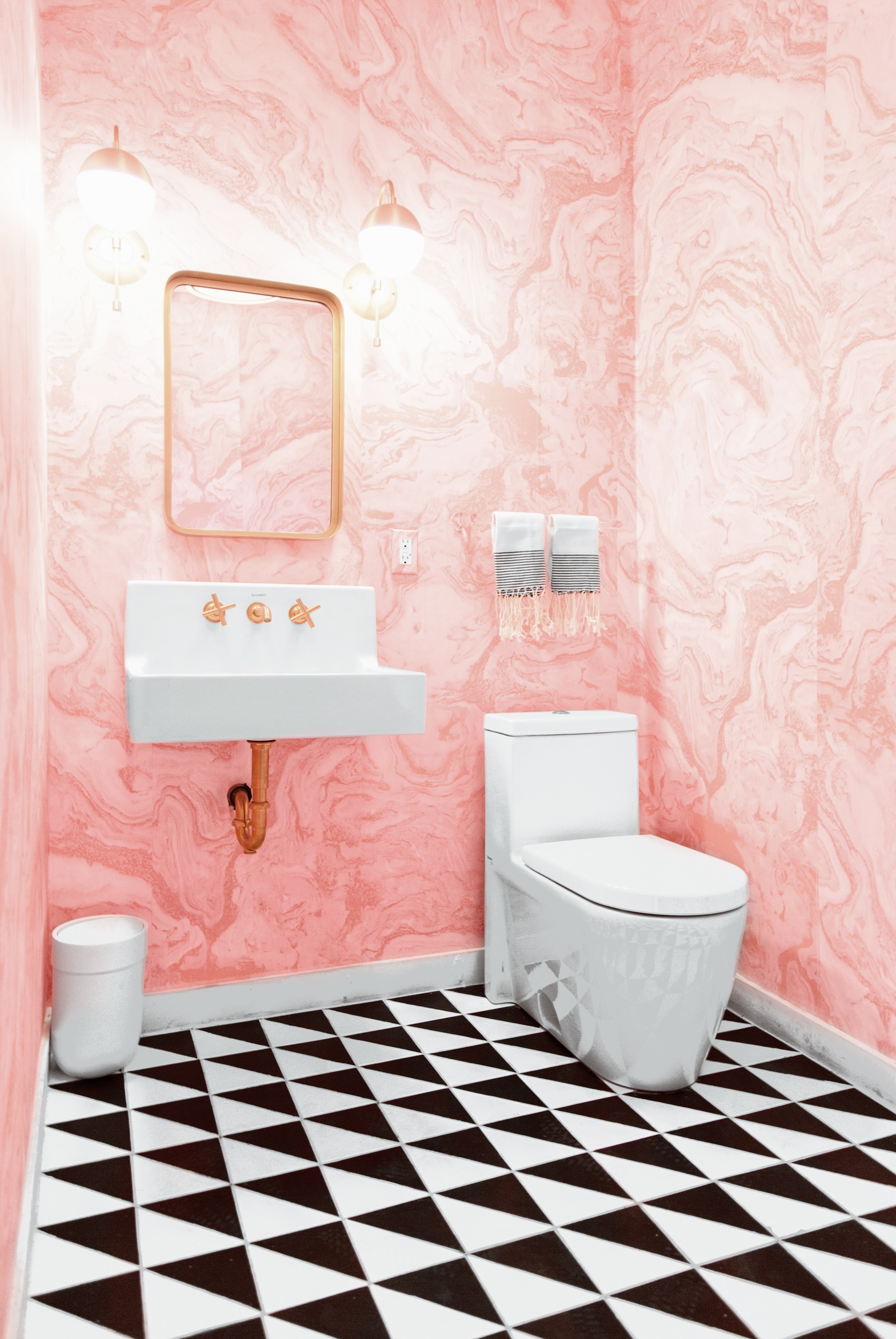 pink bathroom with black and white tile and marble wallpaper and brass accents via @citysage