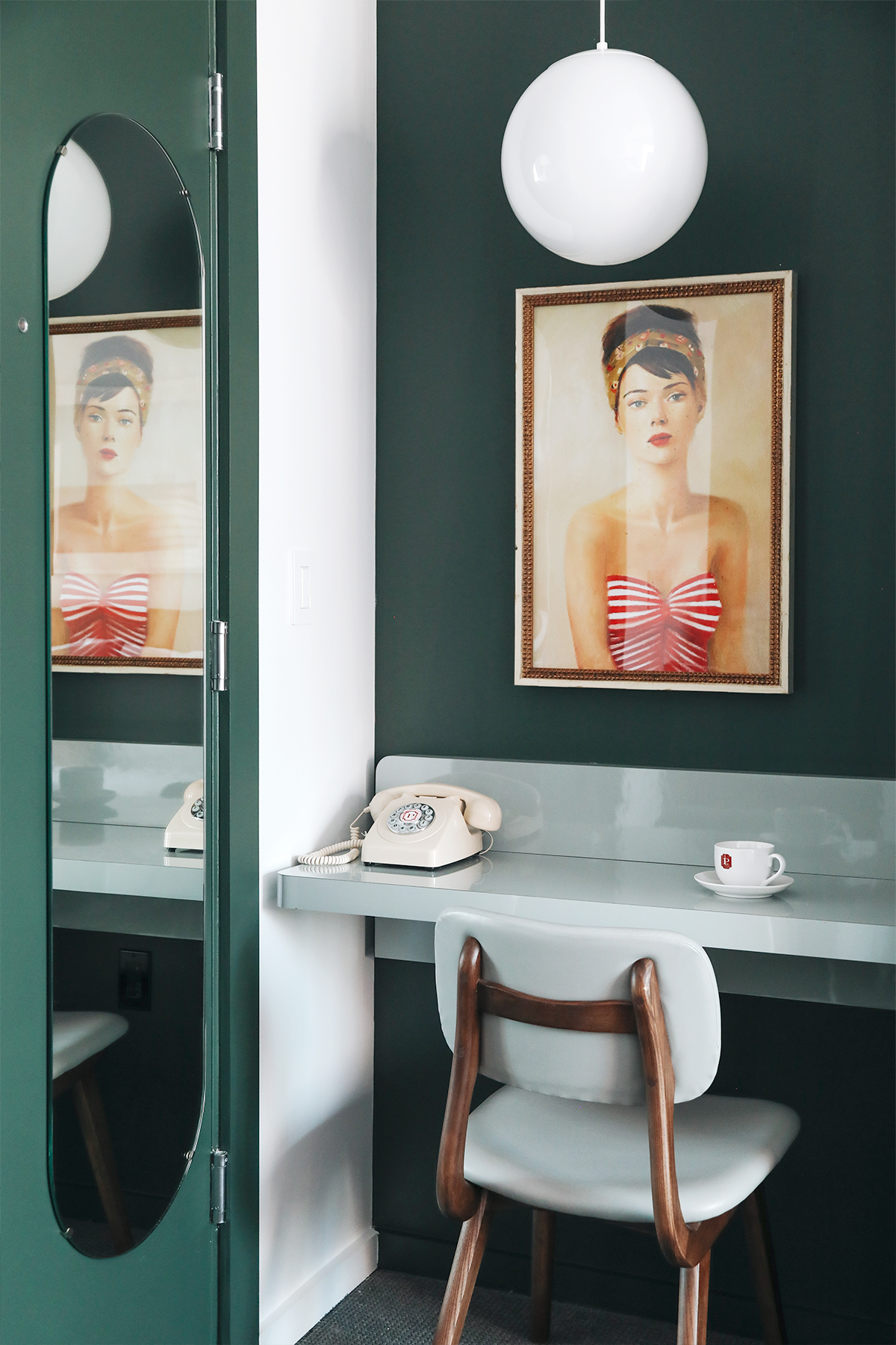 dark green walls with built-in desk and oval mirror
