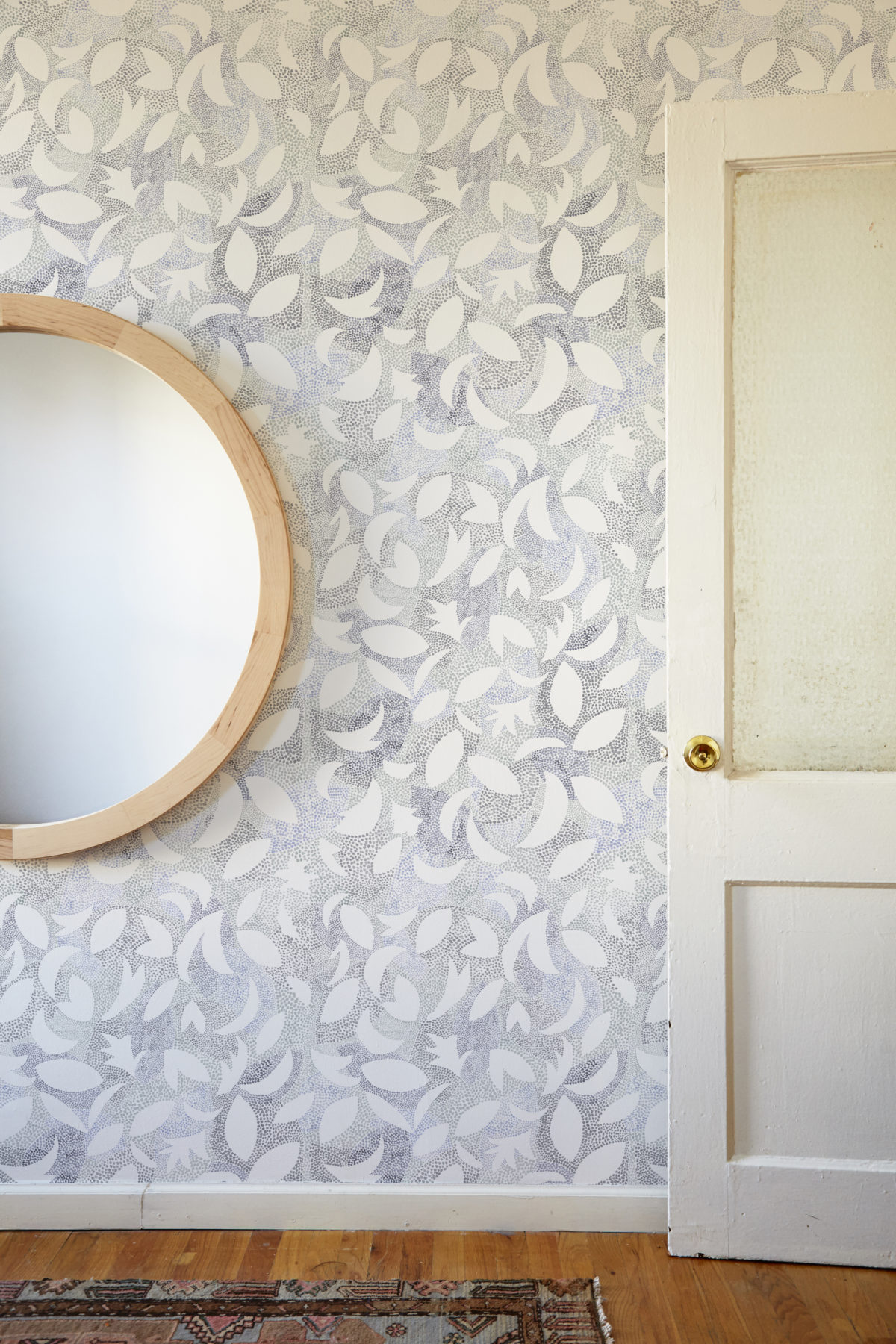 round mirror in an entryway with wallpaper