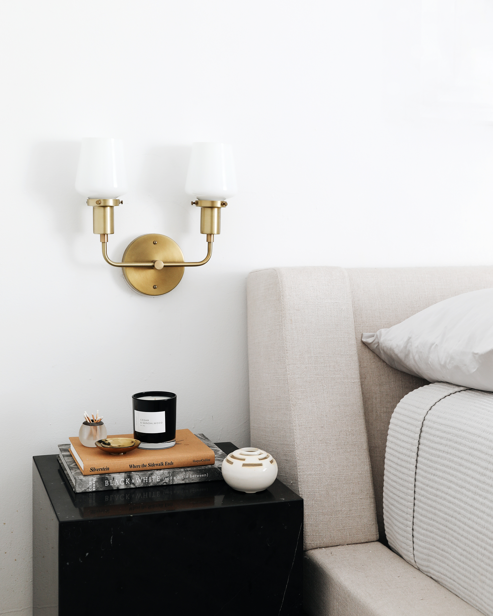 modern upholstered bed and cube nightstand with brass wall sconce