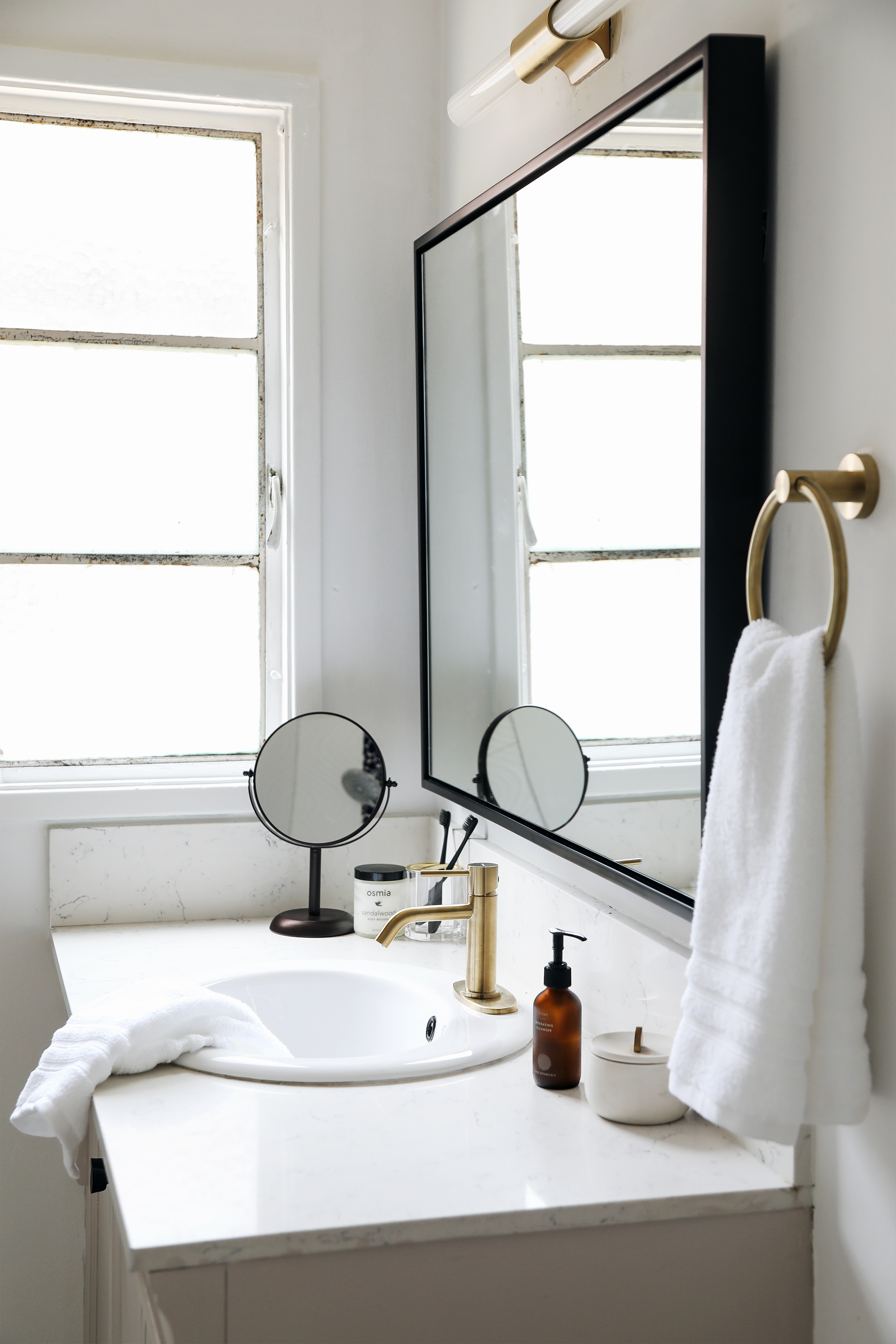 budget bathroom makeover with brass fixtures and black mirror